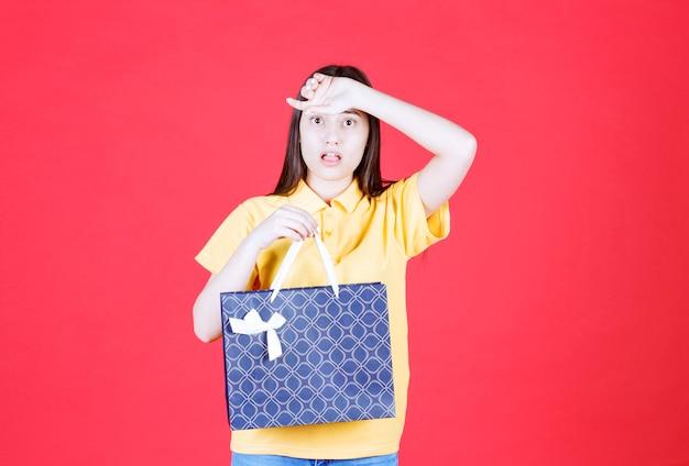 Mädchen im gelben hemd, das eine blaue einkaufstasche hält und erschrocken aussieht.