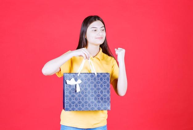 Mädchen im gelben hemd, das eine blaue einkaufstasche hält und positives handzeichen zeigt.