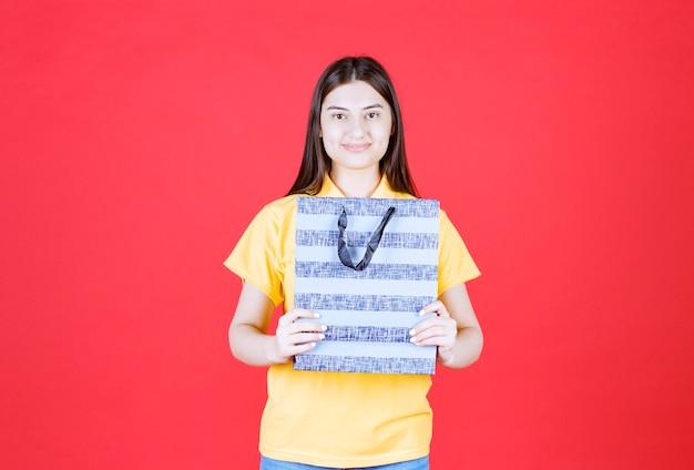 Mädchen im gelben hemd, das eine blaue einkaufstasche mit mustern hält