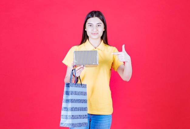 Mädchen im gelben hemd, das eine einkaufstasche und eine silberne geschenkbox hält und ein positives handzeichen zeigt