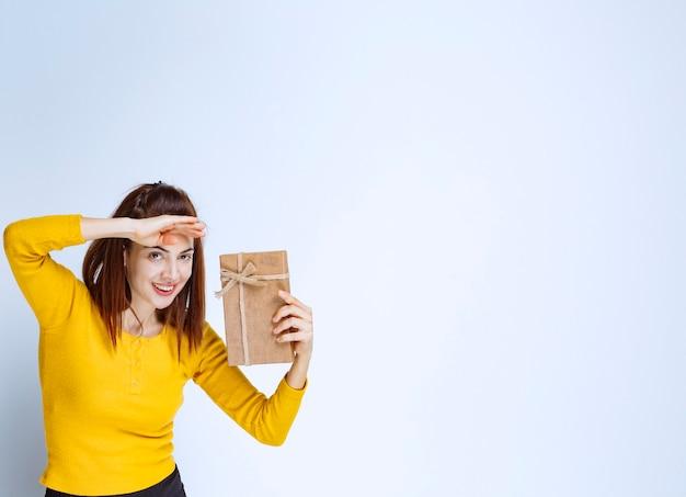 Mädchen im gelben hemd, das eine geschenkbox aus pappe hält und jemanden sucht, um es zu präsentieren.