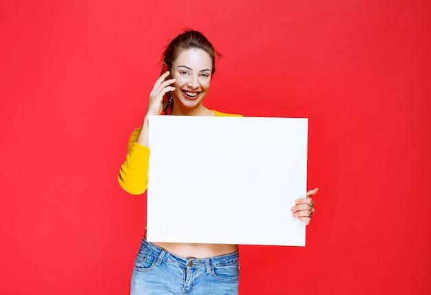 Mädchen im gelben hemd, das eine quadratische infotafel hält und mit dem telefon spricht