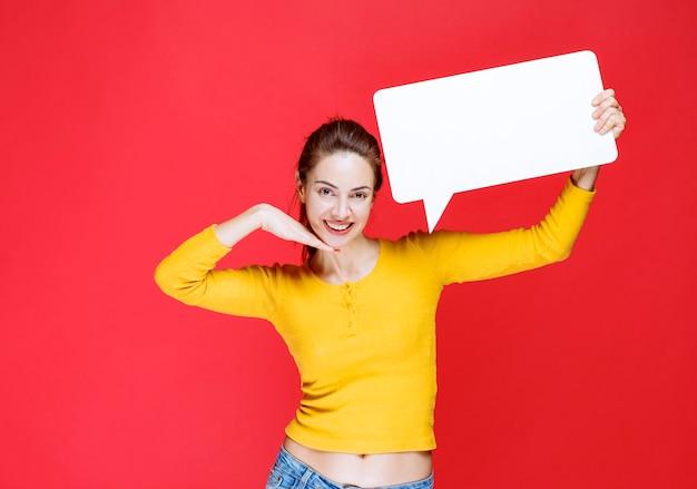 Mädchen im gelben hemd, das eine rechteckige infotafel hält