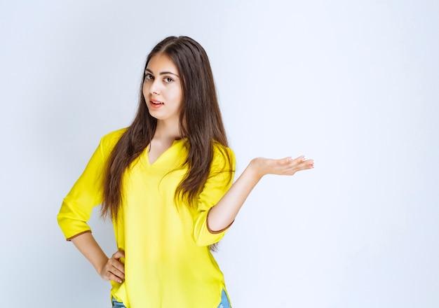 Mädchen im gelben hemd, das etwas in ihrer offenen hand zeigt.