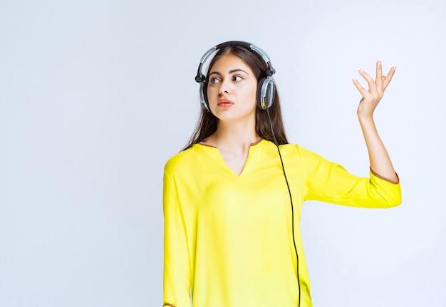Mädchen im gelben hemd, das kopfhörer trägt und verwirrt und verängstigt aussieht.