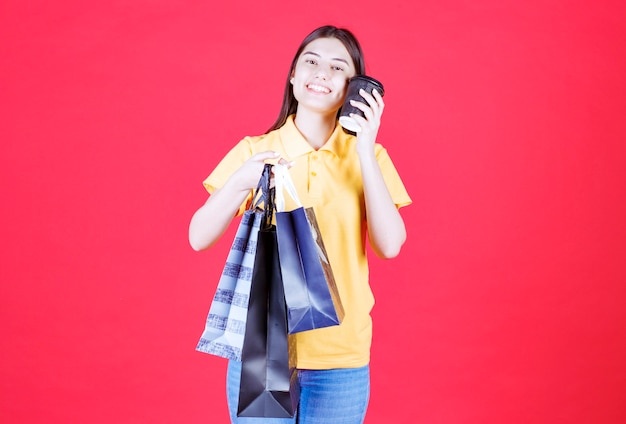 Mädchen im gelben hemd, das mehrere blaue einkaufstaschen hält und eine schwarze tasse getränk hat.