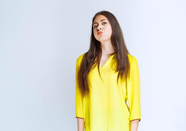 Mädchen im gelben hemd sieht müde aus oder hat kopfschmerzen.