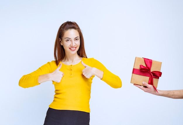 Mädchen im gelben hemd wird eine pappgeschenkbox mit rotem band angeboten und zeigt positives handzeichen.