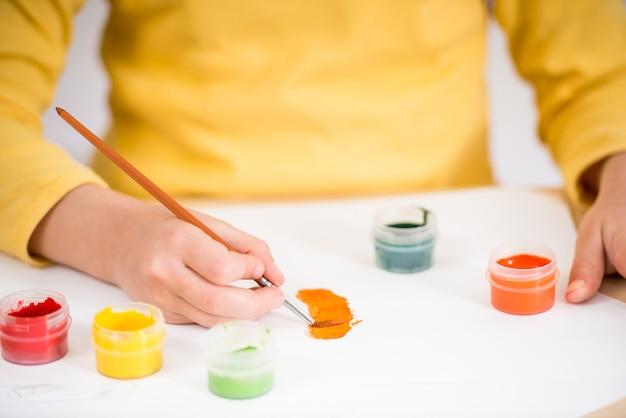 Mädchen im gelben pullover, der bild mit gouachefarben macht.
