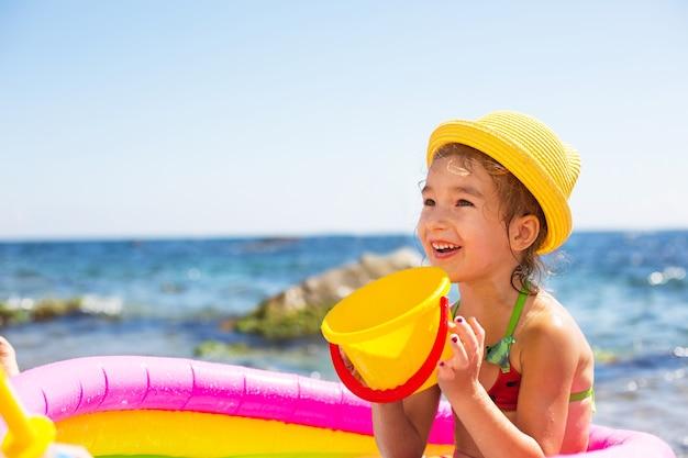 Mädchen im gelben strohhut spielt mit dem wind, dem wasser und einem wasserspender in einem aufblasbaren pool am strand.