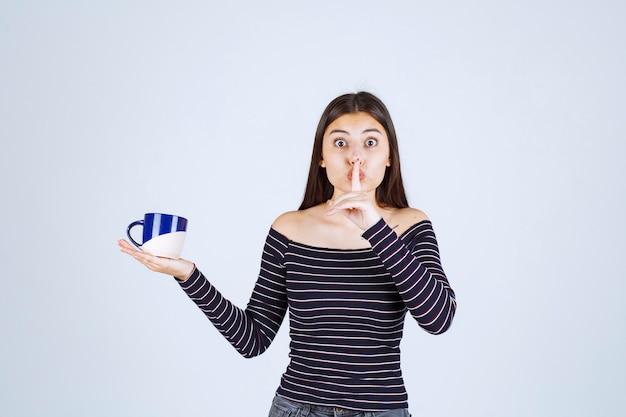 Mädchen im gestreiften hemd, das eine kaffeetasse hält und um stille bittet.