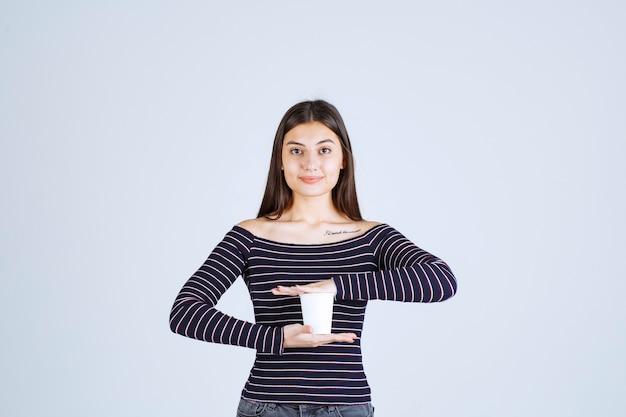 Mädchen im gestreiften hemd, das eine plastikkaffeetasse zwischen ihren händen hält.