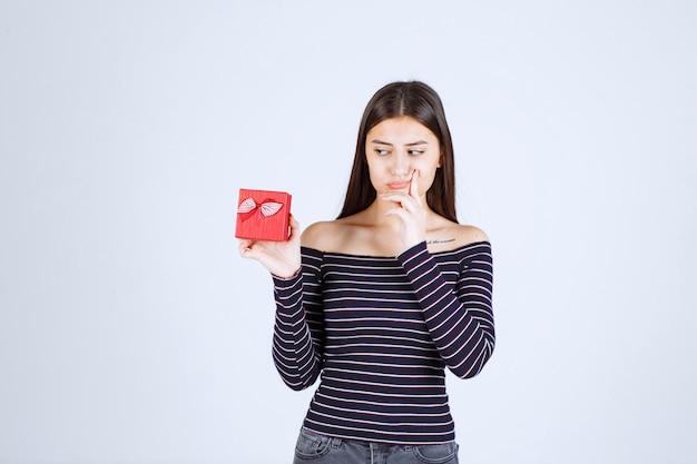 Mädchen im gestreiften hemd, das eine rote geschenkbox hält, sieht verwirrt und zweifelhaft aus.