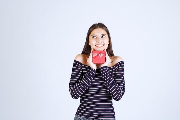 Mädchen im gestreiften hemd, das eine rote geschenkbox hält und aufgeregt schaut.
