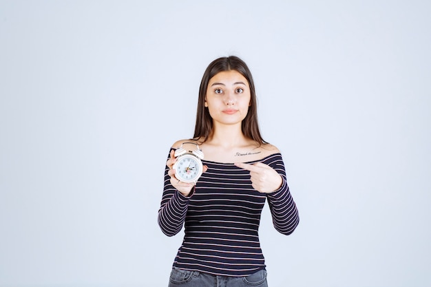 Mädchen im gestreiften hemd, das einen wecker hält und ihn als neues produkt bewirbt.