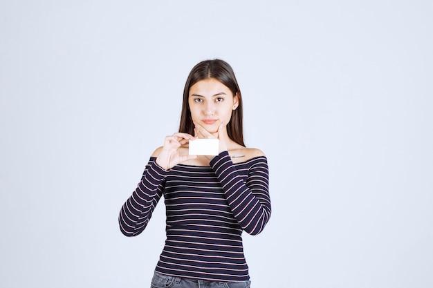 Mädchen im gestreiften hemd hält eine visitenkarte und sieht nachdenklich aus.