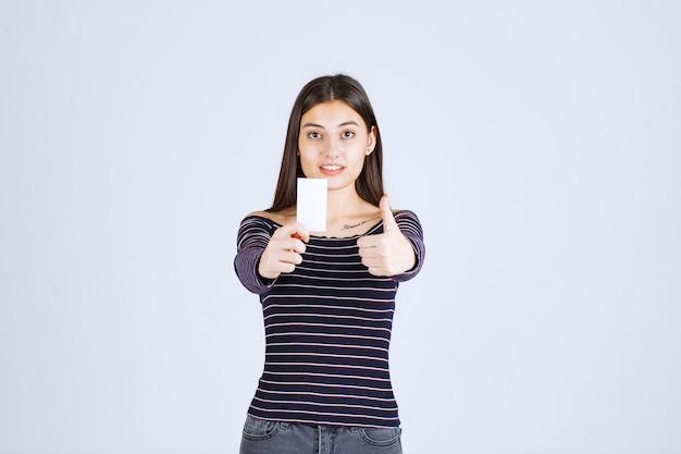 Mädchen im gestreiften hemd hält eine visitenkarte und zeigt daumen hoch zeichen.