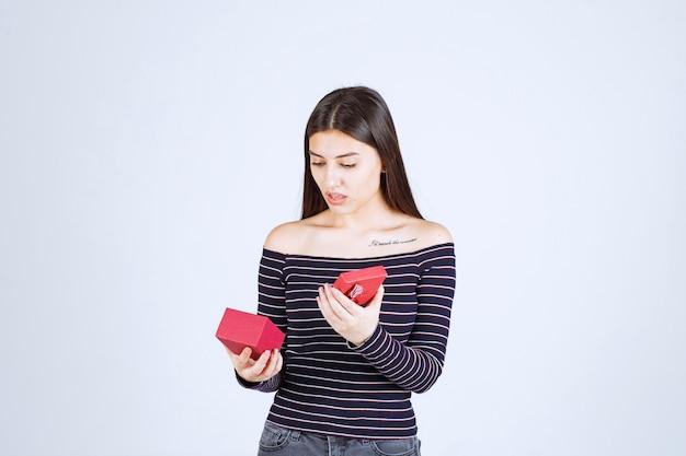 Mädchen im gestreiften hemd öffnet eine rote geschenkbox und wird verwirrt.