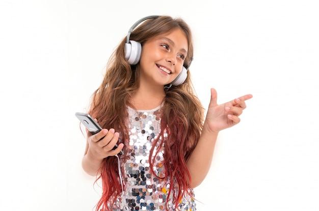Mädchen im glitzernden kleid, mit großen weißen kopfhörern, die musik hören, schwarzes smartphone halten und auf etwas isoliertes zeigen