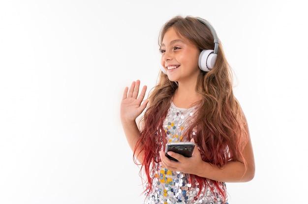 Mädchen im glitzernden kleid, mit großen weißen kopfhörern, die musik hören, schwarzes smartphone halten und mit der hand zu jemandem isoliert winken