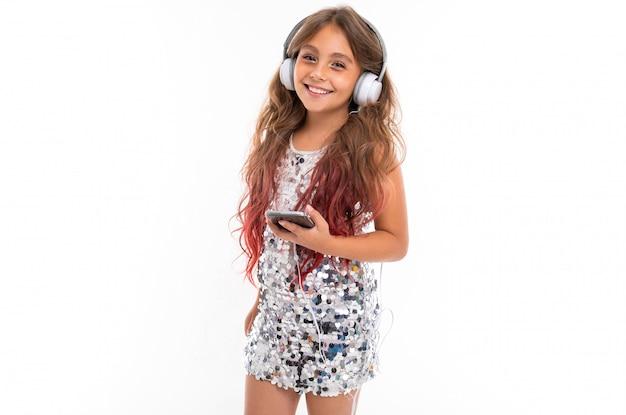 Mädchen im glitzernden kleid, mit großen weißen kopfhörern, die musik hören und schwarzes smartphone isoliert halten