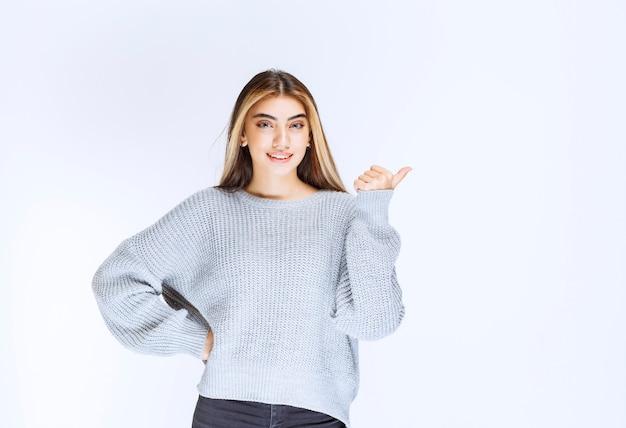 Mädchen im grauen hemd, das auf irgendwo oder auf jemanden zeigt.