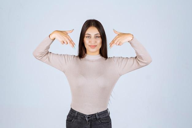 Mädchen im grauen hemd, das auf sich selbst zeigt.