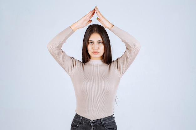 Mädchen im grauen hemd, das dach oder dreieck zeigt.