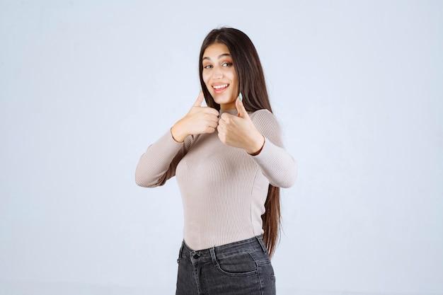 Mädchen im grauen hemd, das daumen hoch macht zeichen.