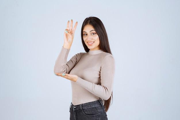 Mädchen im grauen hemd, das drei zahl in der hand zeigt.
