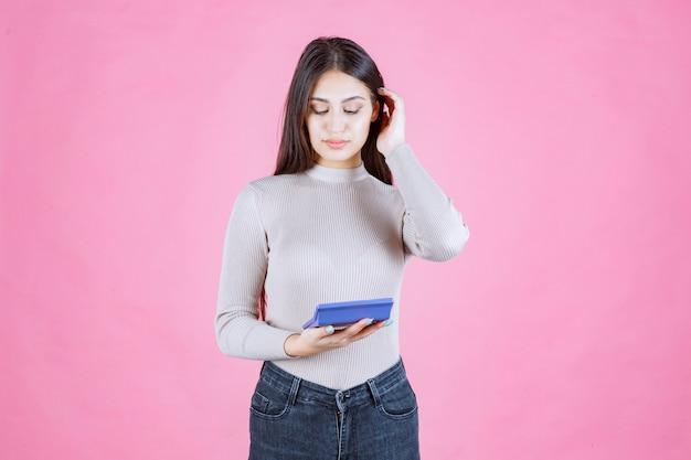Mädchen im grauen hemd, das einen blauen taschenrechner hält, ihn beobachtet und damit arbeitet