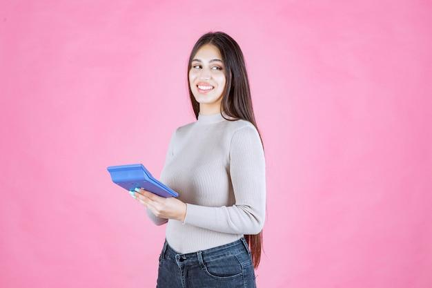 Mädchen im grauen hemd, das einen blauen taschenrechner hält und mit zuversicht lächelt