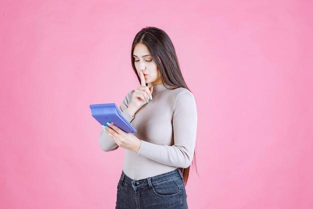 Mädchen im grauen hemd, das einen blauen taschenrechner hält und schweigenzeichen zeigt, während sie arbeitet