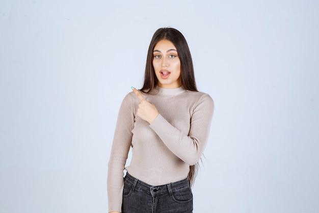 Mädchen im grauen hemd, das etwas auf der linken seite zeigt.
