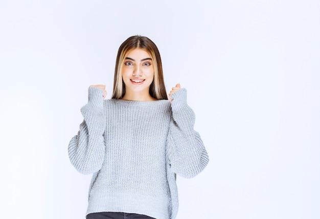 Mädchen im grauen hemd, das glücklich und motiviert aussieht.