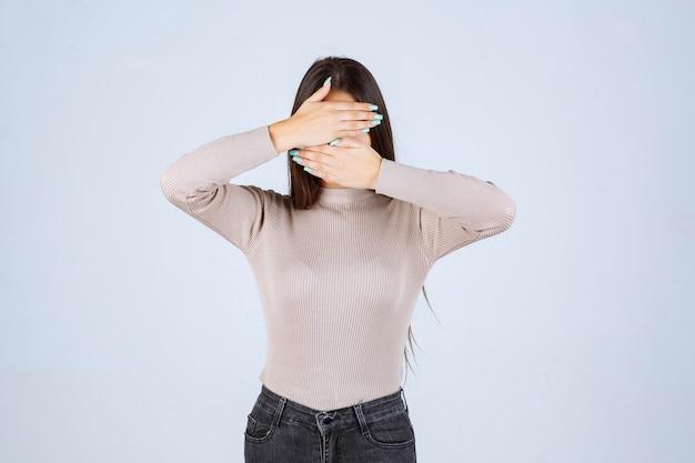 Mädchen im grauen hemd, das ihr gesicht bedeckt und higind.