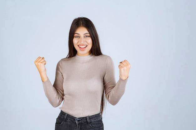 Mädchen im grauen hemd, das ihre armmuskeln zeigt.