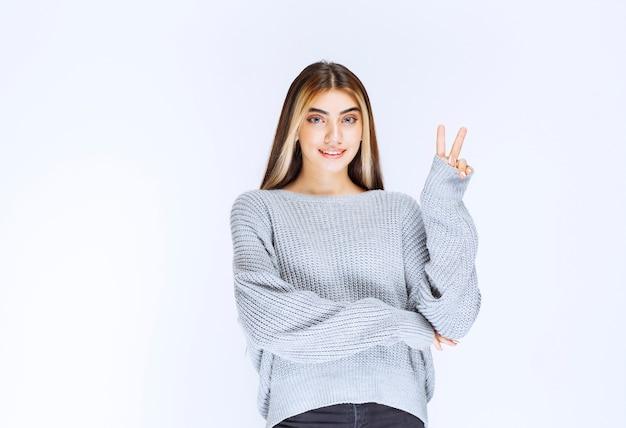 Mädchen im grauen hemd, das sich friedlich und glücklich fühlt.
