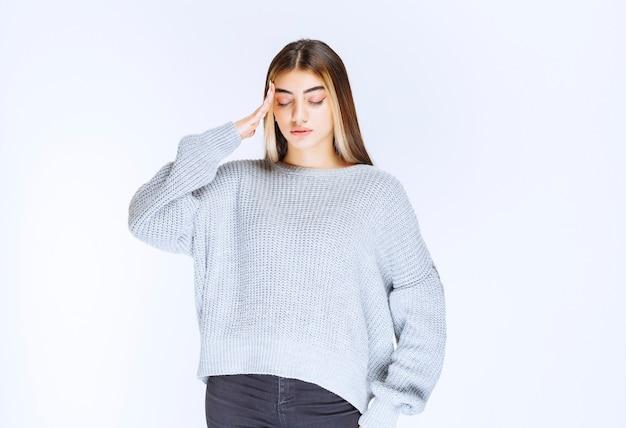 Mädchen im grauen hemd sieht verwirrt aus und denkt nach.