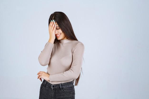 Mädchen im grauen pullover, der ihr gesicht und kopf hält.