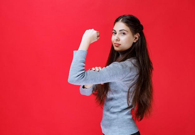 Mädchen im grauen pullover, der ihre armmuskeln zeigt.