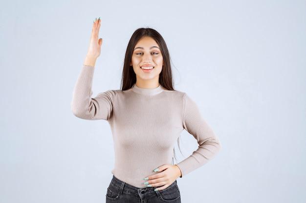 Mädchen im grauen pullover, der ihre hände anhebt.
