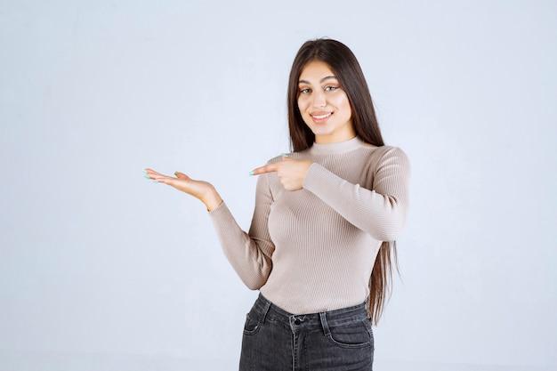 Mädchen im grauen pullover zeigt etwas auf der linken seite.