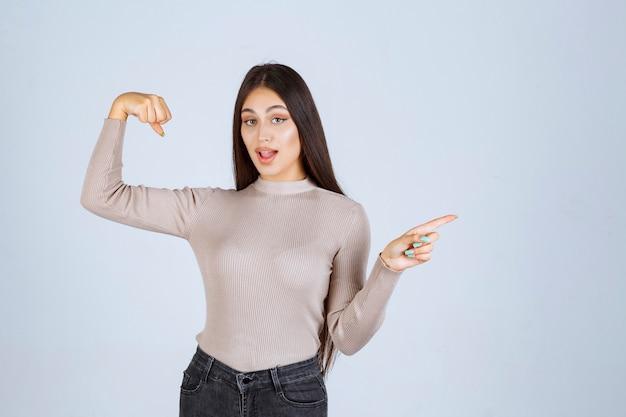 Mädchen im grauen pullover zeigt ihre fäuste und kraft.
