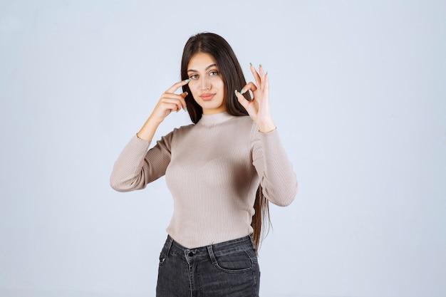 Mädchen im grauen pullover zeigt kreis ok zeichen.