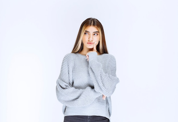 Mädchen im grauen sweatshirt, das denkt und analysiert.