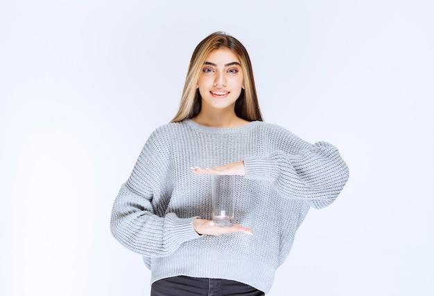 Mädchen im grauen sweatshirt, das ein glas reines wasser hält.