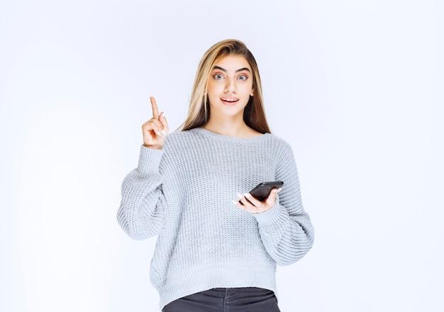 Mädchen im grauen sweatshirt, das ein schwarzes smartphone hält und eine gute idee hat.