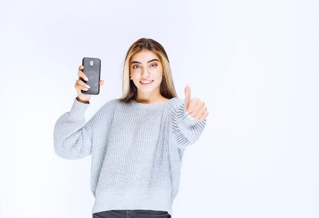 Mädchen im grauen sweatshirt, das ein schwarzes smartphone hält und sich zufrieden fühlt.
