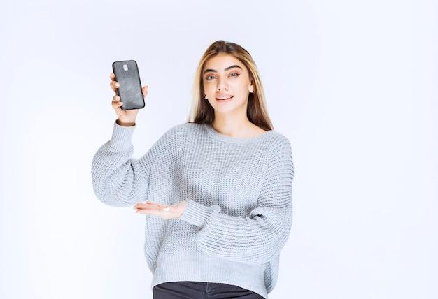 Mädchen im grauen sweatshirt, das ein schwarzes smartphone hält.
